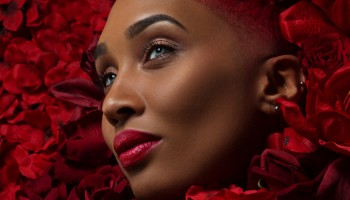 Beautiful mixed race woman in a bed of red flowers