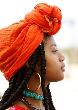 Portrait of a beautiful African American woman wearing an orange head scarf, beaded necklaces and long dreads in an outdoor setting.