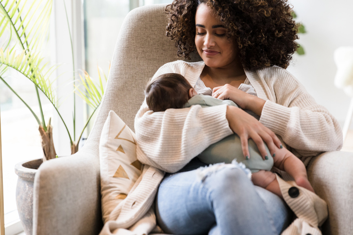 Happy mom breastfeeds her infant son