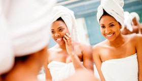 Happy black female friends having fun at a spa talking and smiling