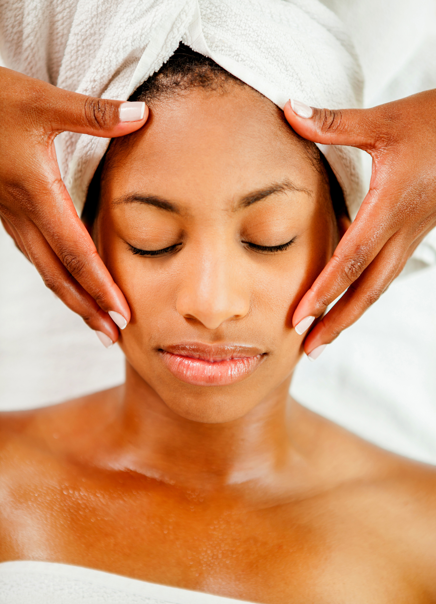 Beautiful black young woman getting a face massage looking very relaxed