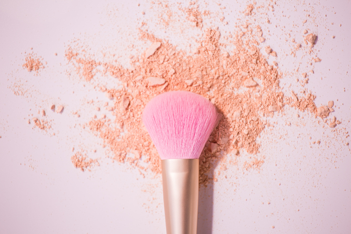Make up brushes with powder on white background