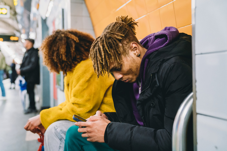 Young man playing with a smartphone while he's waiting for the subway train