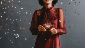 Portrait of an Anonymous Smiling Woman in a Festive Red Dress Holding Sparklers, Celebration Concept