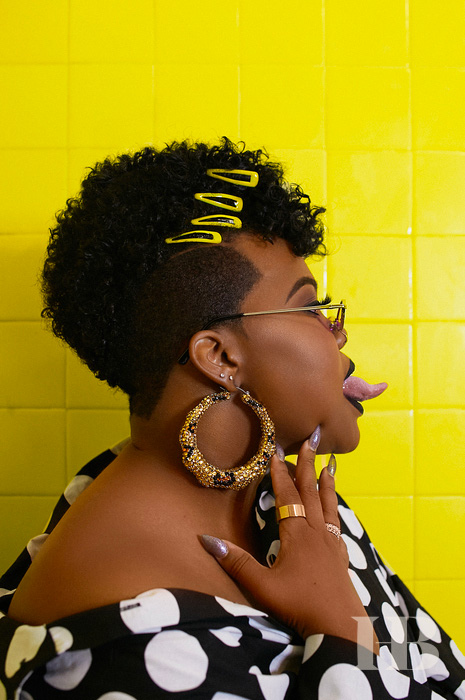A photo silhouette of Amber Riley against a neon yellow and tiled wall.