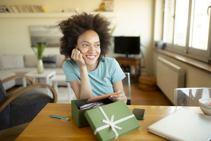 Happy African American woman opening a present