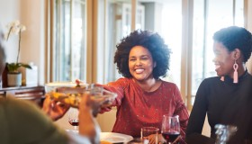 Smiling woman passing food to friend at table
