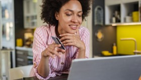 African American woman is shopping online with credit card in the kitchen