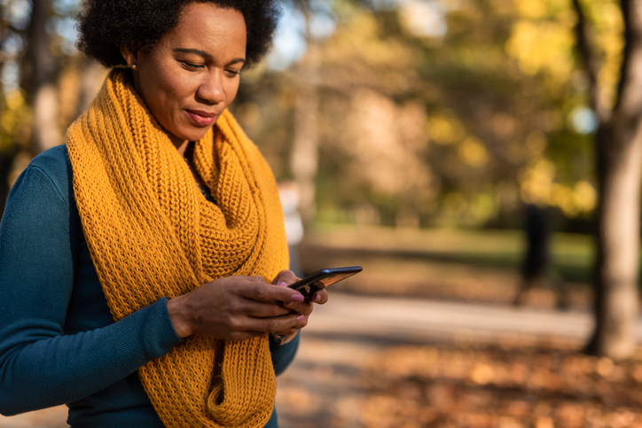African American woman using mobile phone at public park.