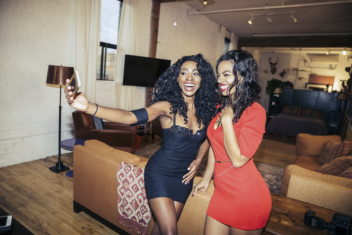 Happy young women taking selfie during party at home