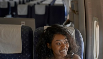 Smiling young woman looking through window while sitting in airplane