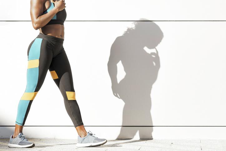 Sportswoman in sports clothing walking against white wall
