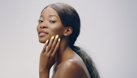 Dreamy african ethnicity woman face skin care. Smoothing skin