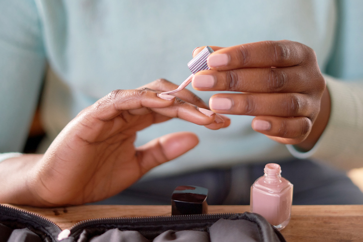 A close-up of a woman painting her nails