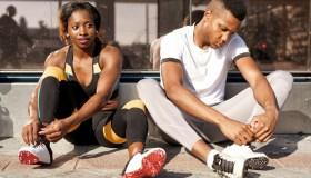 Athletes tying shoelaces while sitting on sidewalk at city