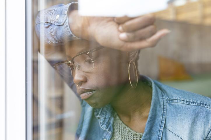 Sad woman looking through window