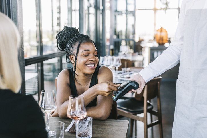 Happy African American woman using credit card