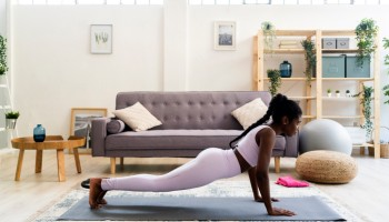 Young woman doing yoga in living room at home