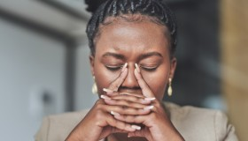 Shot of a young businesswoman stressed woman sitting at her desk in her office