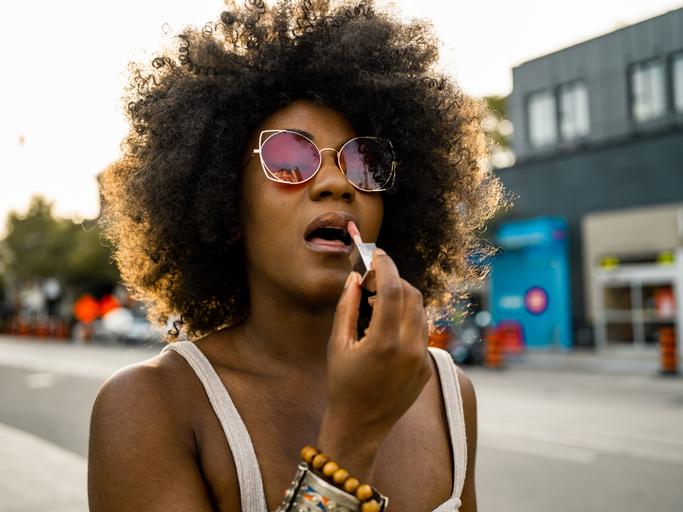 Young black woman on city street adjusting lipstick