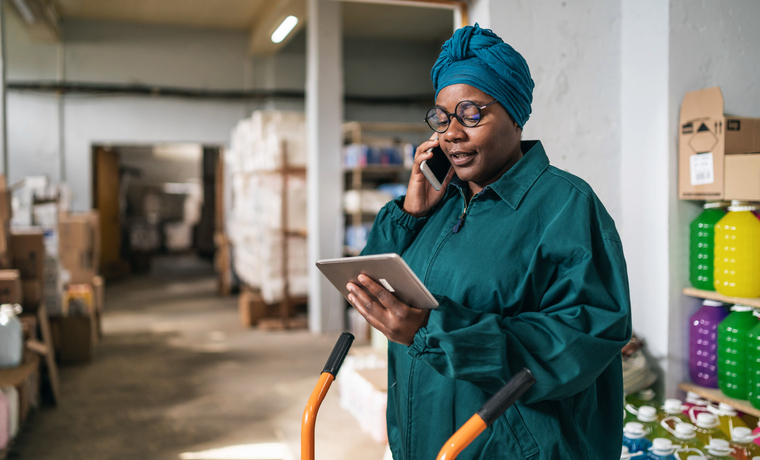 Afro female warehouse manager using a hand truck and talking on a smart phone in distribution warehouse
